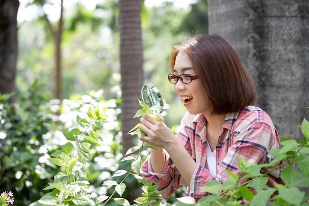 아시아 과학자 아름다운 여자는 돋보기를 사용하여 정원에서 붉은 꽃을 연구