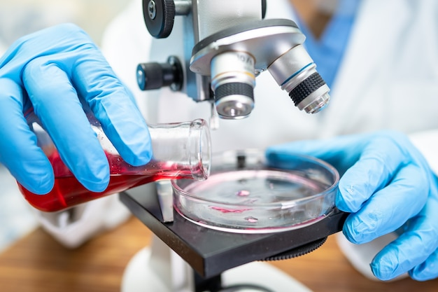 Asian scientist biochemist or microbiologist working research with a microscope in laboratory.