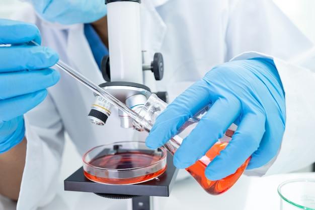 研究室で顕微鏡を使って研究を行っているアジアの科学者生化学者または微生物学者