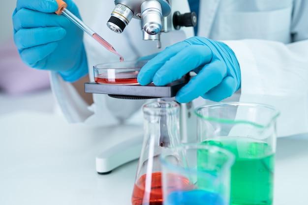実験室で顕微鏡を使って研究を行っているアジアの科学者生化学者または微生物学者