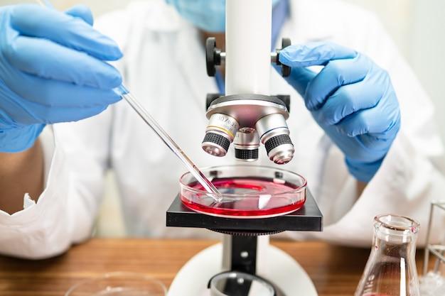 Азиатский ученый работает под микроскопом в лаборатории.