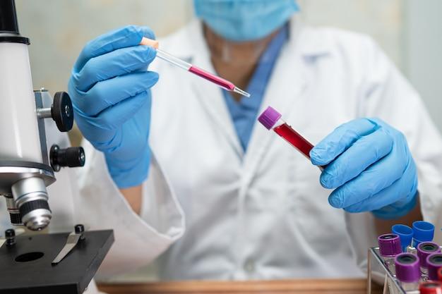 실험실에서 현미경을 사용하는 아시아 과학자.
