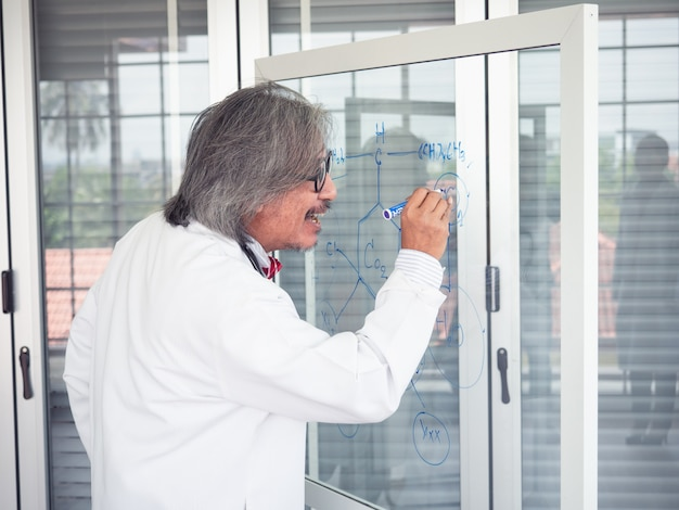 Asian scientist writes a formula on a glass board