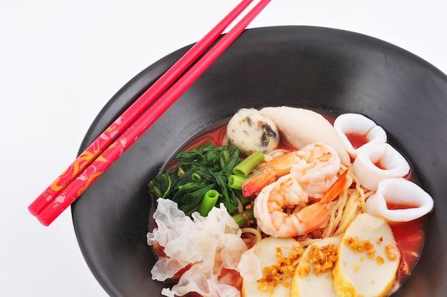 箸のクローズアップとアジアのシーフードヌードルスープ