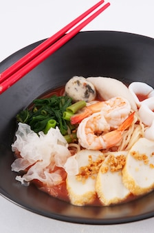 白い背景の箸でアジアのシーフードヌードルスープ