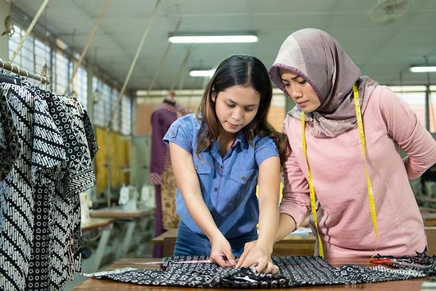 アジアの針子と作業監督者は、規則に従って定規で生地を測定します