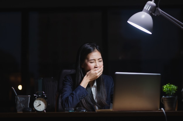 Asian secretary girl working late sitting on desk feeling sleepy in office at night. business woman tired and exhausted work hard for company