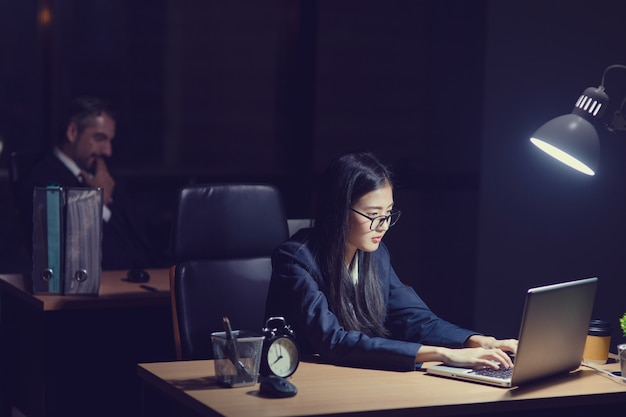 Asian secretary girl working late sitting on desk in office at night. business woman typing on laptop front her boss caucasian boss manager