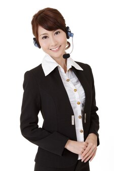 Asian secretary woman with headphone smiling and looking at you, half length closeup portrait on white wall..