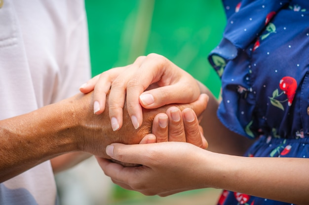 Азиатские старшие и азиатские молодые держась за руки.
