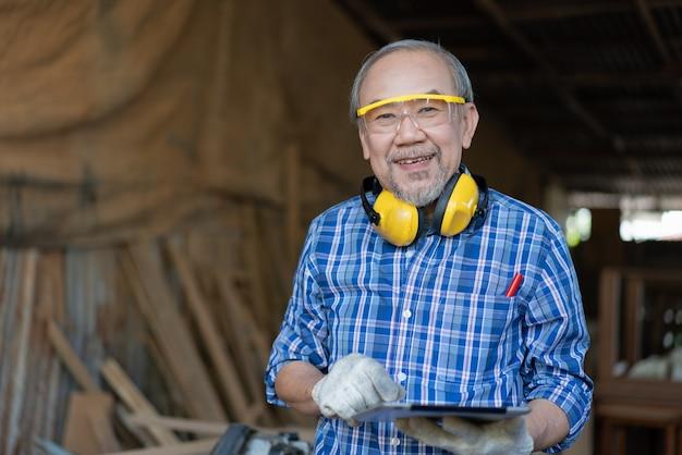 목공 작업장에서 일하는 태블릿 컴퓨터를 들고 웃고 있는 아시아 수석 목수 프리미엄 사진