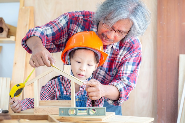 木工店で木の家のおもちゃのサイズを測定するアジアの小さな女の子の職人を教えるアジアのシニア大工の男。