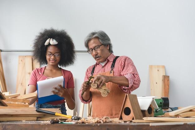 Азиатский старший плотник учит молодую девушку ремеслу
