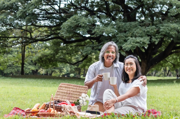 Asian senior couple drinking coffee and picnic at park.