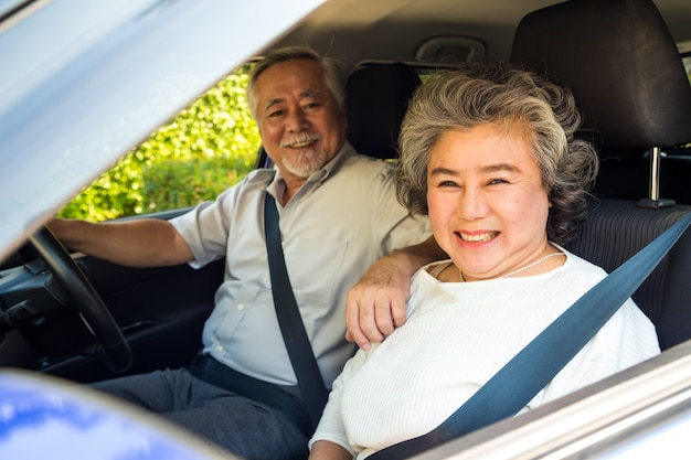 Asian senior couple driving a car and smile happily with glad positive expression during the drive to travel journey, people enjoy laughing transport on road trip concept