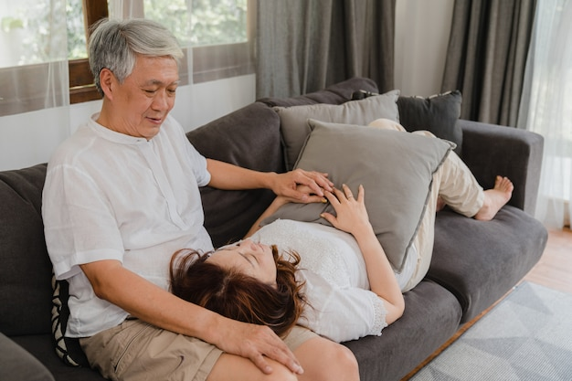 Asian senior couple relax at home. asian senior chinese grandparents, husband happy smile hug lie down her wife lap while lying on sofa in living room at home concept.