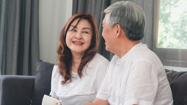 Asian senior couple relax at home. asian senior chinese grandparents, husband and wife happy smile hug talking together while lying on sofa in living room at home concept.