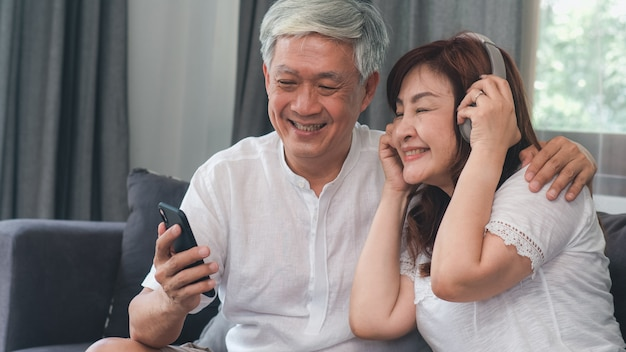 Asian senior couple relax at home. asian senior chinese grandparents, husband and wife happy wear headphone using mobile phone listen to music while lying on sofa in living room at home concept.
