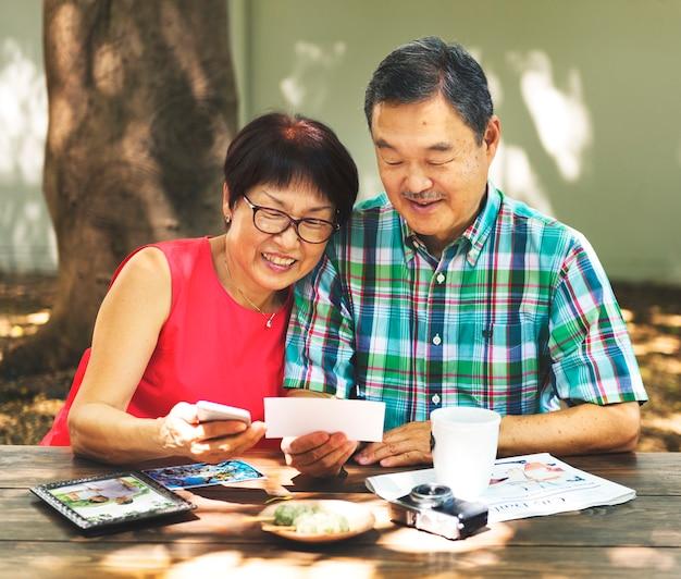 Asian senior couple reminiscing photos concept