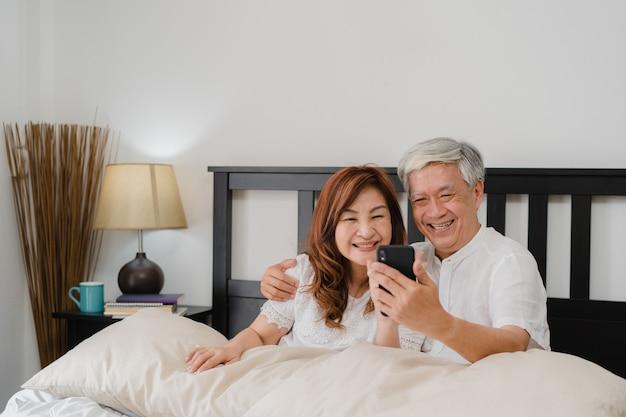Азиатское старшее selfie пар дома. азиатские старшие китайские деды, супруг и жена счастливые используя selfie мобильного телефона после бодрствования лежат на кровати в спальне дома в концепции утра.
