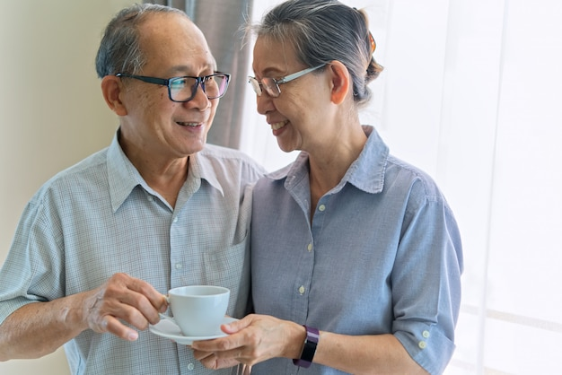 Asian senior couple smiling and looking on each other.