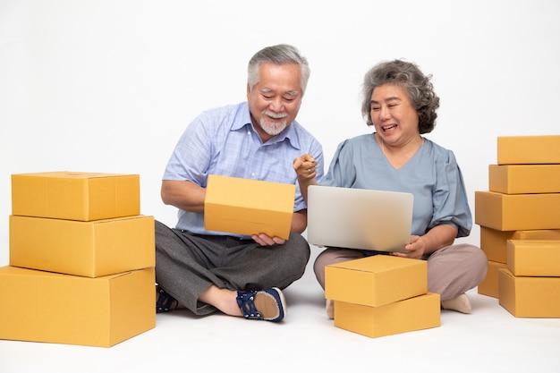 Азиатский старший пара запуска малого бизнеса фриланс с коробкой посылки и ноутбуком компьютера и сидя на полу, изолированных на белой стене, онлайн маркетинг концепции упаковки коробки доставки концепции