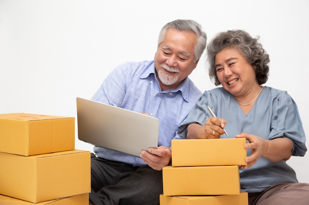 Asian senior couple startup small business freelance with parcel box and computer laptop and sitting on floor isolated on white wall, online marketing packing box delivery concept