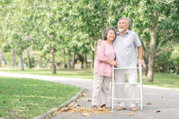 公園でウォーカーと散歩を話しているアジアのシニアカップル