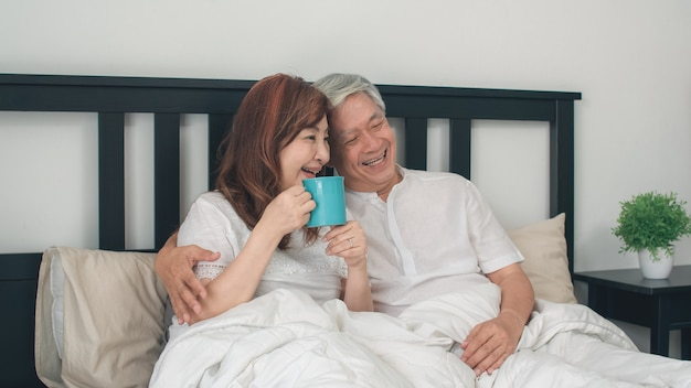 Asian senior couple talking on bed at home. asian senior chinese grandparents, husband and wife happy drink coffee after wake up while lying on bed in bedroom at home in the morning concept. Free Photo
