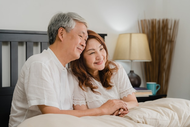 Asian senior couple talking on bed at home. asian senior chinese grandparents, husband and wife happy relax together after wake up while lying on bed in bedroom at home in the morning concept.