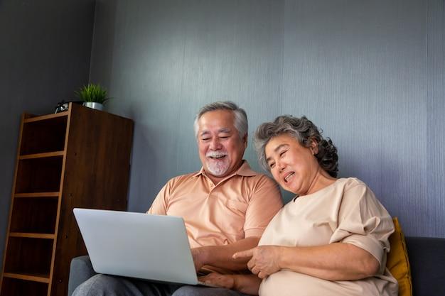 ラップトップコンピューターでビデオ通話チャットで話しているアジアの年配のカップル、高齢者のためのスマートテクノロジー、オンラインコンセプトの接続概念を維持