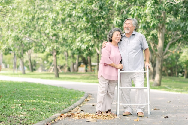 Asian senior couple talking a walk with walker in the park
