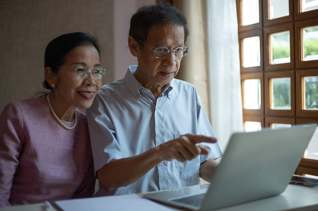 Asian senior couple using laptop computer for vdo call with their family.