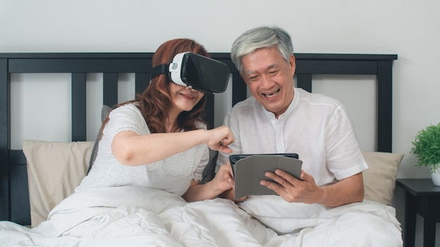 Asian senior couple using tablet at home. asian senior chinese grandparents, feeling happy fun and vr playing games together while lying on bed in bedroom at home in the morning concept.