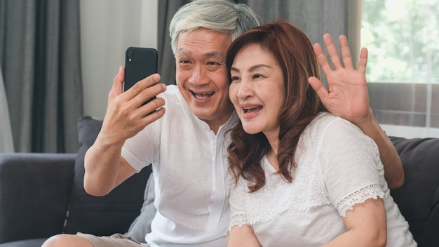 Asian senior couple video call at home. asian senior chinese grandparents, using mobile phone video call talking with family grandchild kids while lying on sofa in living room at home concept.