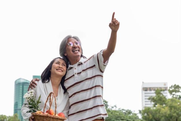 公園でフルーツバスケットライフスタイル幸福とアジアシニアカップル。
