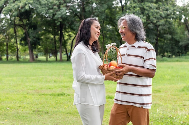 Asian senior couple with fruit basket lifestyle happiness in park.