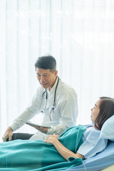 Asian senior doctor sitting on hospital bed and discussing with female patient