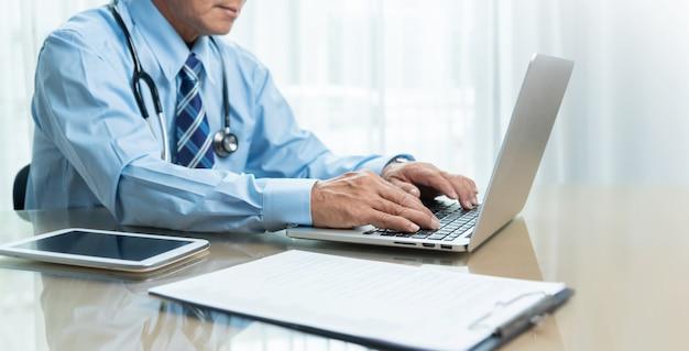 Азиатский старший доктор используя портативный компьютер, цифровую таблетку и доску сзажимом для бумаги на столе в медицинской комнате.
