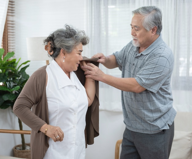 Asian senior elder man help elder woman wear a shirt at home.