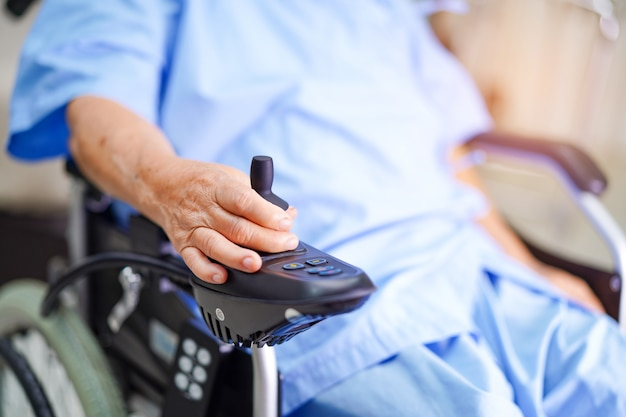 Asian senior or elderly old lady woman patient on electric wheelchair with remote control at nursing hospital ward.