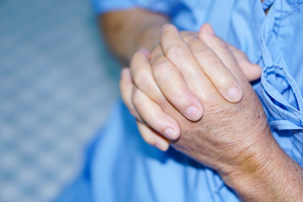 Asian senior or elderly old lady woman patient hold her hand with hope while sitting