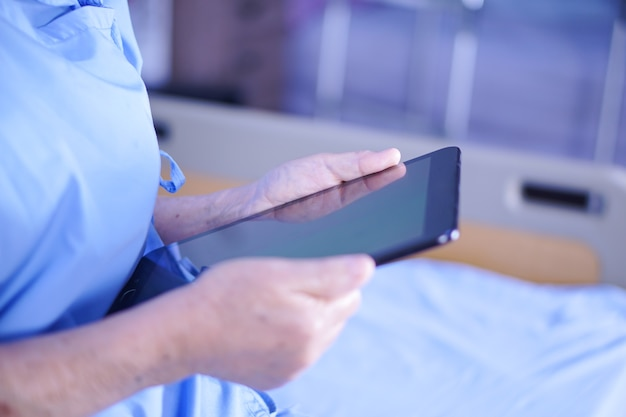 Asian senior or elderly old lady woman patient holding in her hands digital tablet.