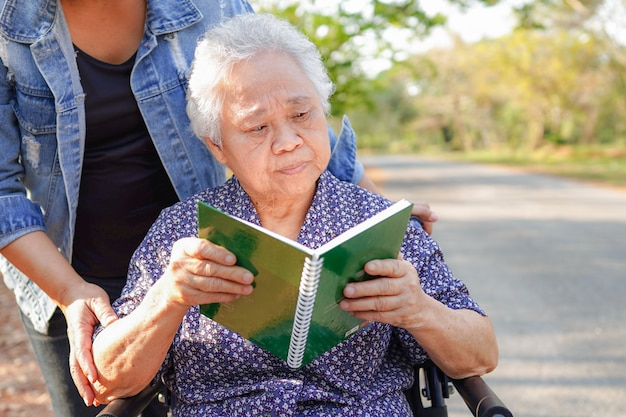 Asian senior or elderly old lady woman patient reading a book while sitting on wheelchair in park : healthy strong medical concept