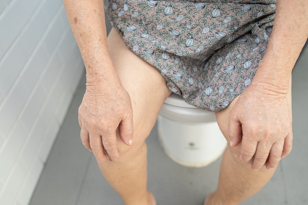 Asian senior or elderly old lady woman patient sitting on flush toilet in bathroom.