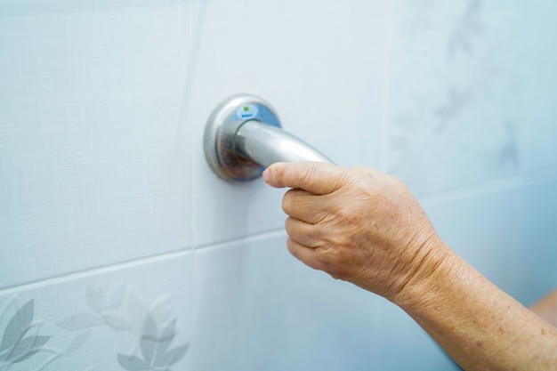 Asian senior or elderly old lady woman patient use toilet handle security in nursing hospi
