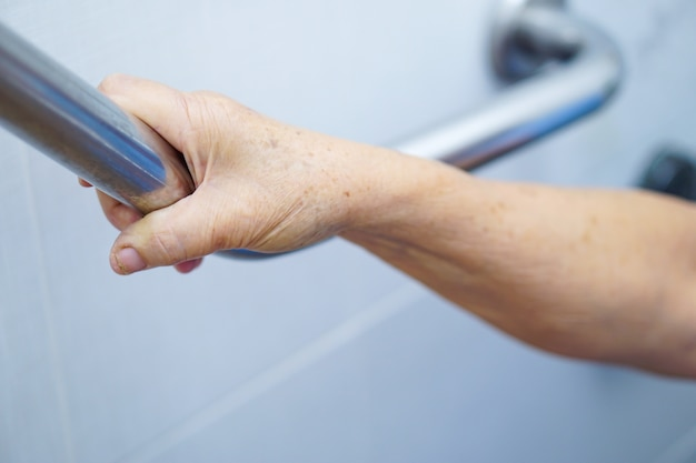 Asian senior or elderly old lady woman patient use toilet handle
