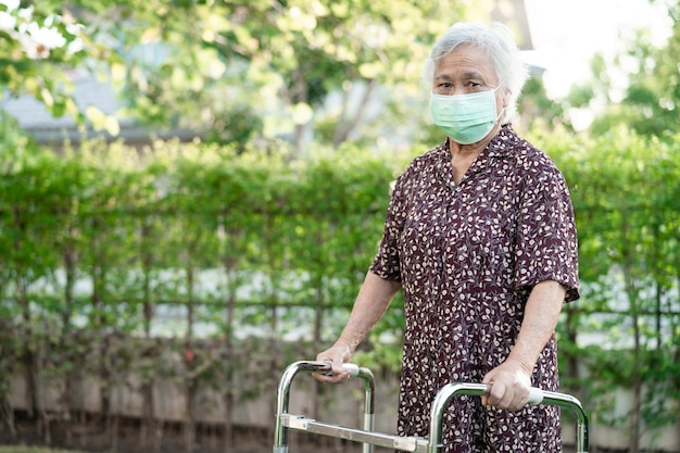 Asian senior or elderly old lady woman patient walk with walker in park with copy space healthy strong medical concept