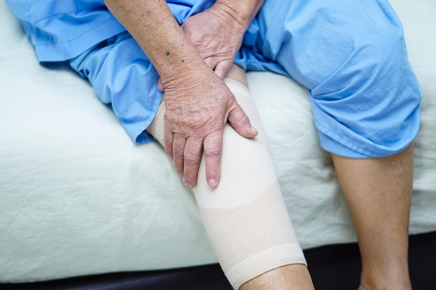 Asian senior or elderly old lady woman patient with knee support pain joint.