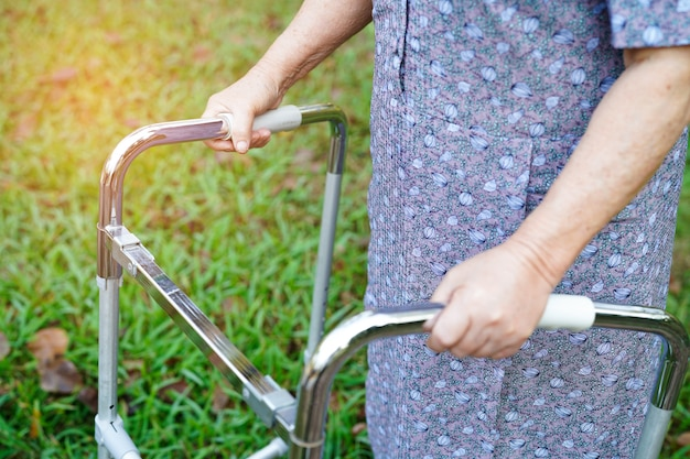 Asian senior or elderly old lady woman use walker with strong health while walking at park in happy holiday